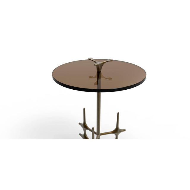 The Ico drinks table with a uniquely designed wax cast bronze base and refined and formative finial supporting a glass...