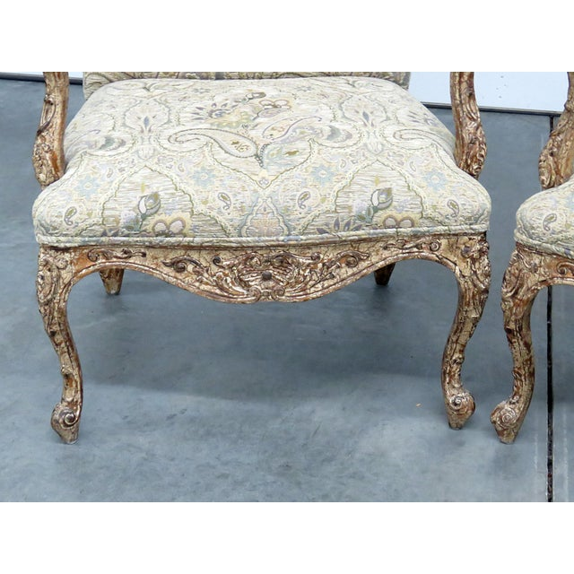 Pair of Louis XV style machined tapestry upholstered armchairs with distressed frames.