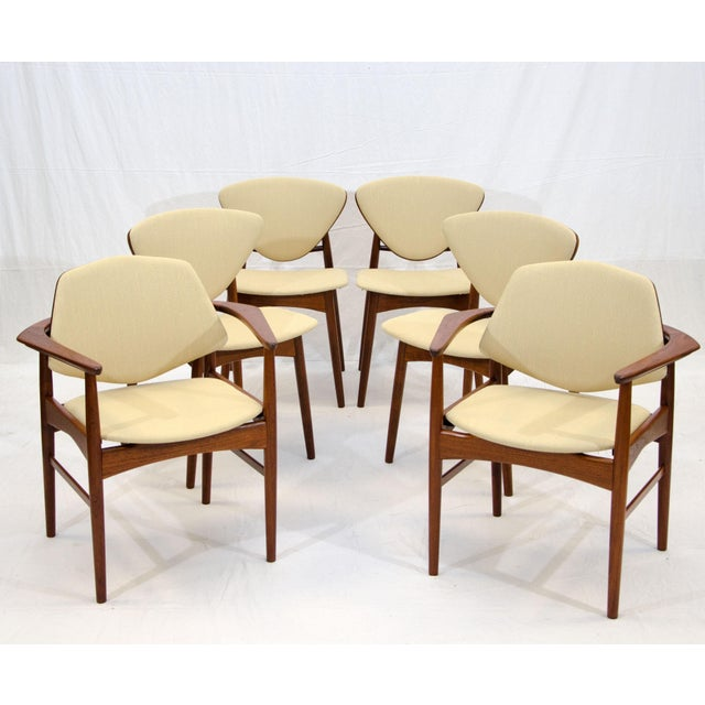 """Unusual chairs with upholstered seats and back fronts, the rear of the chair backs are teak. There is a """"Made in Denmark""""..."""