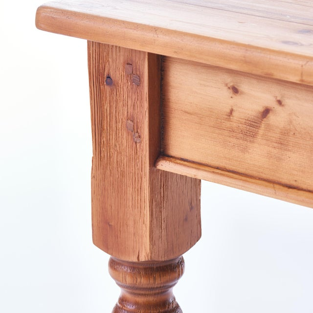 Rustic Amish-made pine farm table dating from the early 1900's. The table features two drawers for storage, and voluptuous...