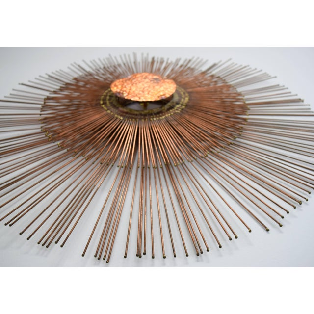 Striking copper wall sunburst wall sculpture by Curtis Jere. Two tiers of copper rods radiate around a central copper...