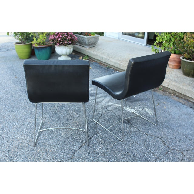 Pair of modern black leather ligne roset French chairs with metal legs.