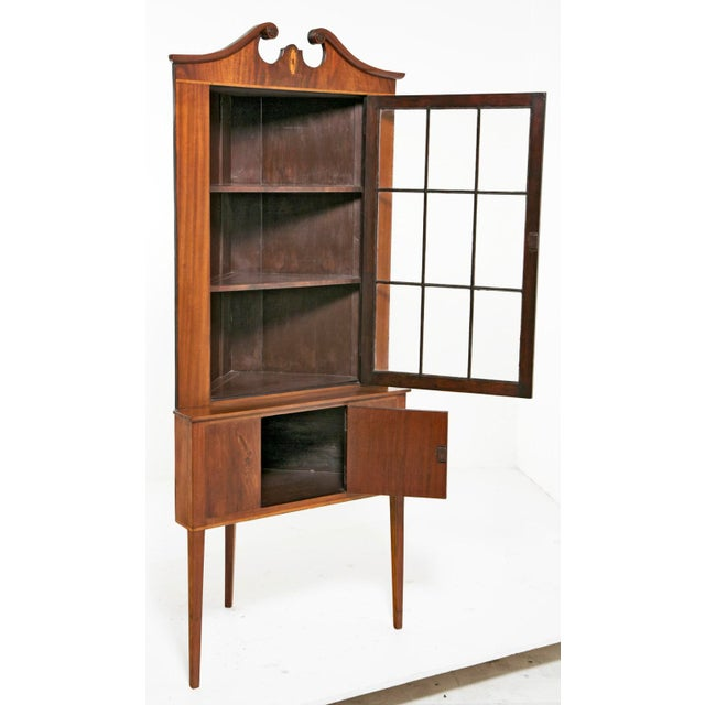 A handsome pair of Federal style corner cabinets in mahogany with boxwood and satinwood inlays and crowned with broken...