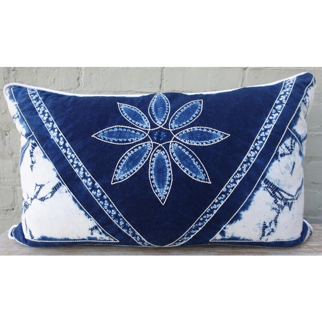 Rectangular blue & white batik pillow with large blue daisy-like flower with white stitched petals inside a triangular...
