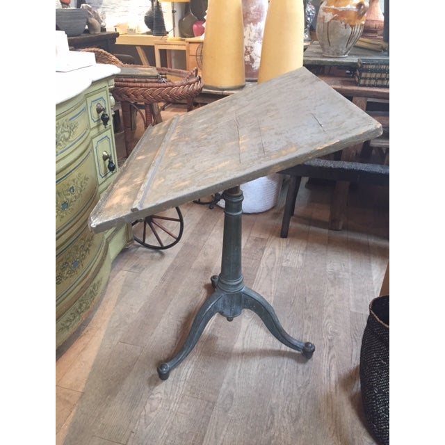 A vintage adjustable drafting table with great patina and iron base and gears adjustable.