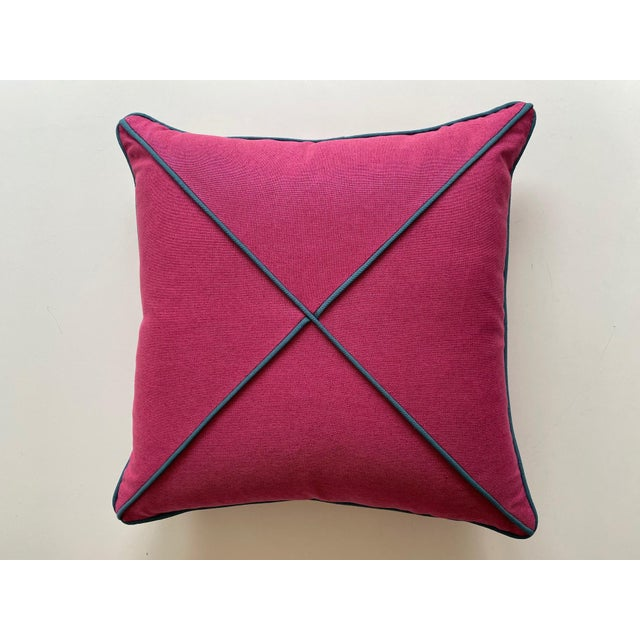 A pair of fuchsia and peacock blue square pillows. The tailored pillows are the perfect size for club chairs, a sofa or an...