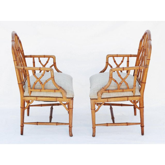 Pair of armchairs, of pine, carved as bamboo, in the Chippendale style, with a back inset with triple Gothic-arch, its...
