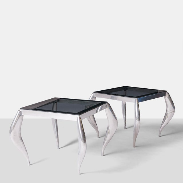 A pair of polished aluminum and smoked glass side tables in the style of Jordan Mozer. Wavy legs support the glass surface...