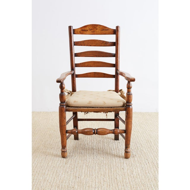 Large 19th century English carved oak armchair featuring a ladder back design and a rush seat. Sits on massive turned legs...