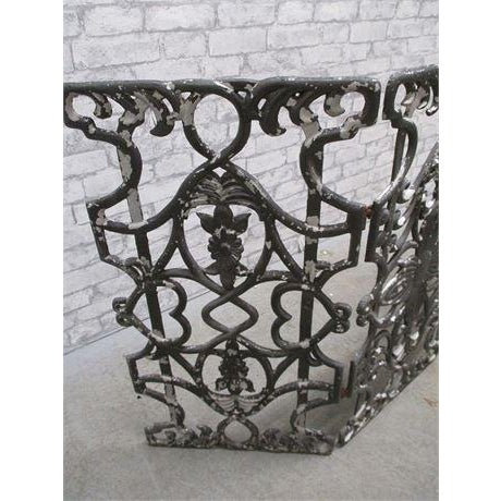 This is an antique ornate fireplace screen from the early 20th century. The piece features beautiful weathered patina....