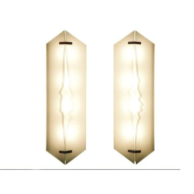 Pair of wall lights Glass, sandblasted glass, lacquered steel Italy, circa 1960 Measures: H 62 x W 17 x D 10 cm H 24 3/8 x...