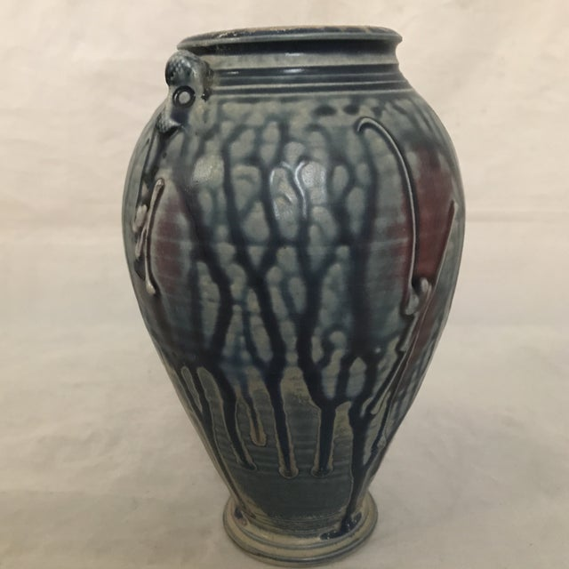 Artisan crafted pottery vase with blue and purple drip glaze finish has unique pair of fish head (?) handles. A one-of-a-...