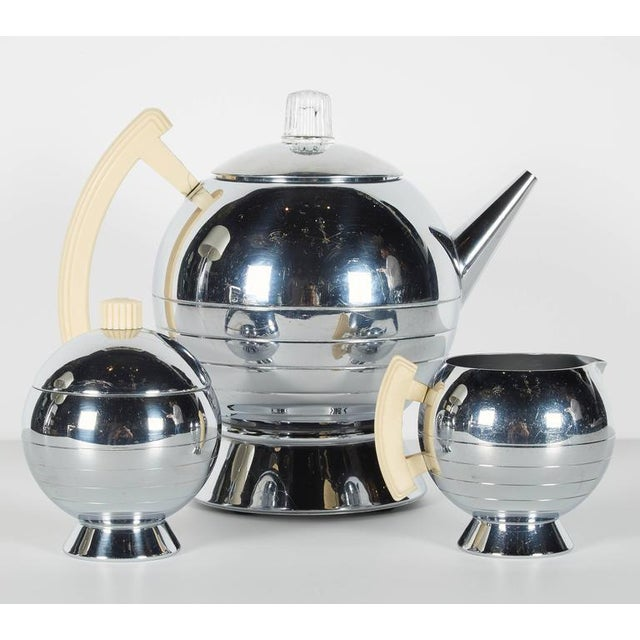 Iconic Art Deco coffee and tea service set with stylized Machine Age design. All pieces have chrome finish with bakelite...
