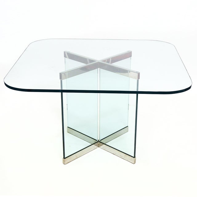 A very refined design, this dining table By Leon Rosen has a glass base in an X form with chrome fittings at the top and...