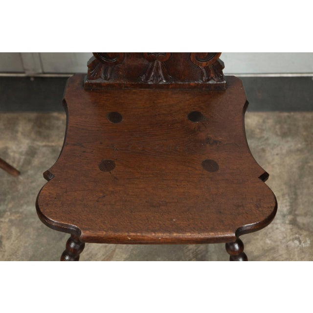 A nice pair of carved, pierced oak hall chairs with turned legs that point outward in the Tyrolean style. Austria, late...