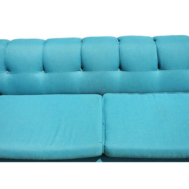 This long Mid-Century Modern sofa is upholstered in its original turquoise fabric and features a tufted back and angular...