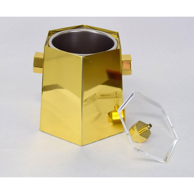 Polished brass and Lucite hexagonal ice bucket with hexagonal handles and finial. Faceted Lucite lid sits elegantly on...