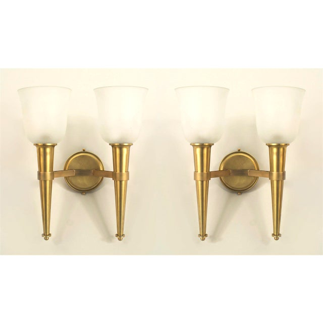 Two pair of French 1940s brass two torch design arm wall sconces supporting shaped frosted glass shades with a round...