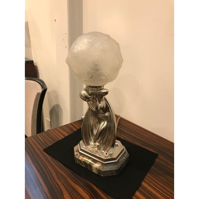 """Beautiful French Art Deco table lamp signed by Sabino. Having a deco bronze female sitting on a """"Potoro"""" marble base. The..."""