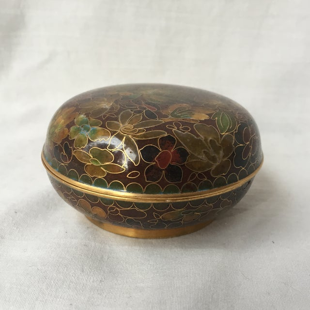 Wonderful vintage lidded box with intricate enamel work known as cloisonné. The dish has a lovely warm color scheme and is...