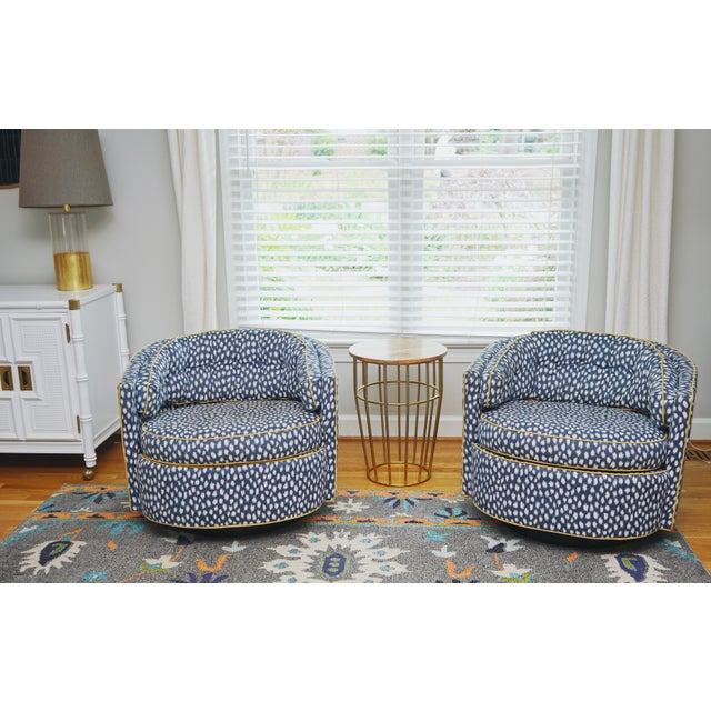 This is a pair of midcentury swivel chairs in the style of Milo Baughman with a wood plinth base. They have been...