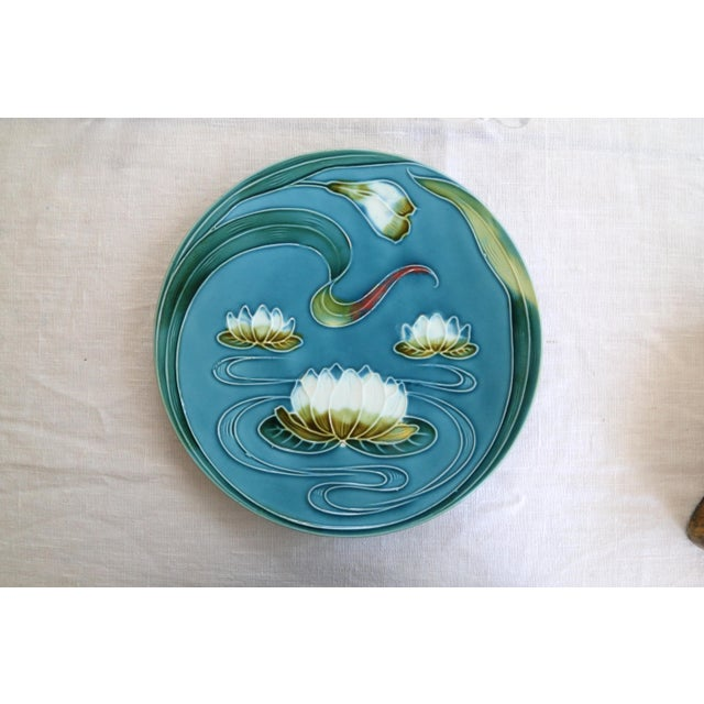 Set of four, Art Nouveau-style German Majolica plates hand-painted with white lily pads on a turquoise-hued field.