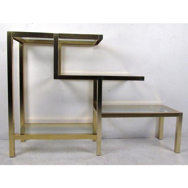 Vintage-modern Milo Baughman style bookcase featuring sculpted body with brass finish and four glass shelves, circa 1970s....