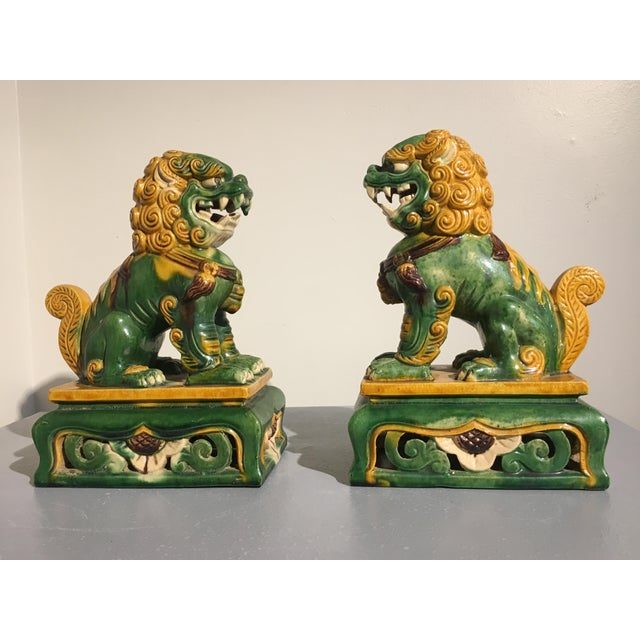 A charming and well molded pair of 1920's Chinese guardian lions covered in an attractive three color, or sancai, glaze,...