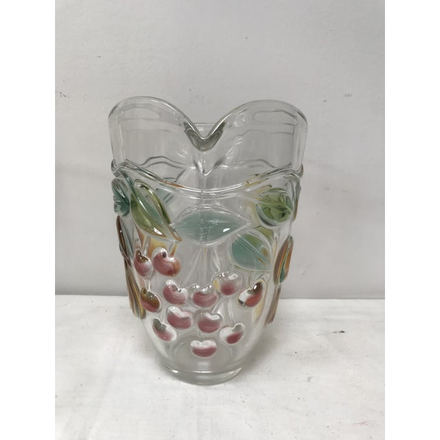 Vintage, handled glass pitcher in clear glass with fruits in different colored glass. Pears, cherries, apples.