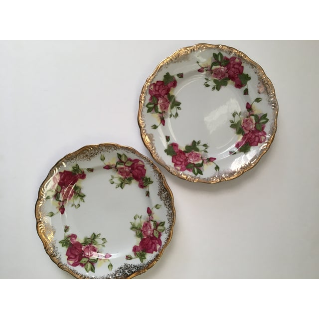 The pair of salad sized plates have a lovely rose pattern & golden detailed edge. There are no markings on them.