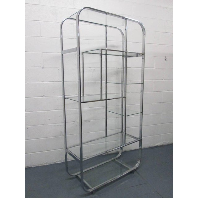 Chrome Etagere with glass shelving. Has curved corners to the top and bottom.