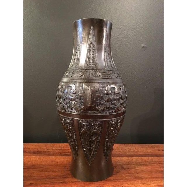 The vase of elegant ovoid baluster form and featuring well cast archaistic designs. The main design cast as a pair of...