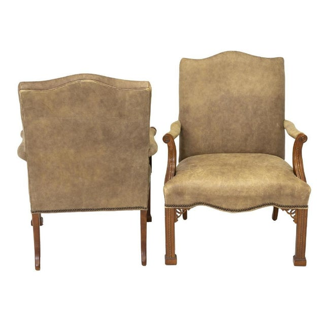 A pair of Chinese Chippendale style highback arm chairs upholstered in leather, 20th c. The arm chairs feature arched...