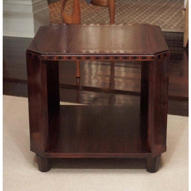 Two-tier side table in mahogany; canted corners; the top apron with a band of ebony and fruitwoods; hexagonal feet.