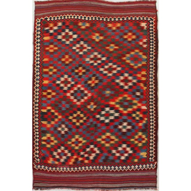 Antique hand-knotted Persian Qashqai kilim rug, circa 1920. Bold palette features deep red, blue, green, and cream. 6'x9'