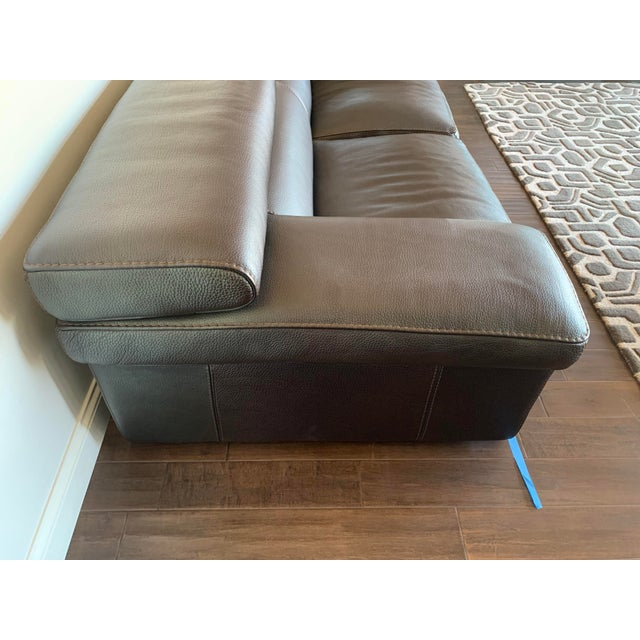 The sectional is upholstered in a rich brown leather with stitching. Featuring wide flat armrests and headrest. It is very...