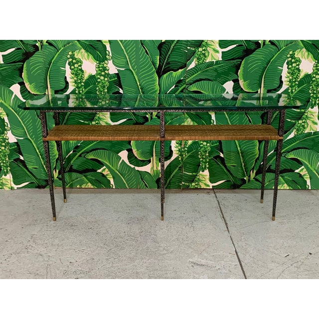 Mixed media console table features a metal frame with diamond cut detailing, brass accents, rattan center shelf, and a...