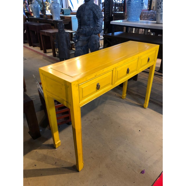 Beautiful distressed yellow console table with 3 drawers. Handcrafted in China with solid elm wood and antique brass ring...
