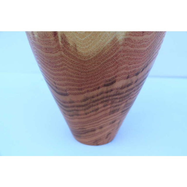 A hand-turned vase by the noted Florida wood turner John Mascoll out of honey locust. The top finial is fitted in not...