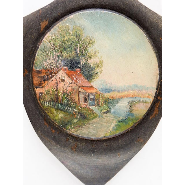 Small circa 1920's oil on wood painting of rustic cabin and landscape. Unsigned, painted on shield shaped wood plaque,...