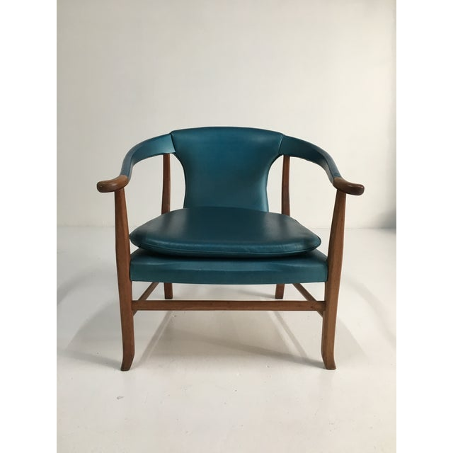 Lovely walnut slipper chair with in a sleek Ming-inspired style with upholstered horseshoe arms that terminate in a...