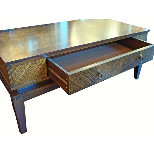 A Mid-century style coffee table made of warm glowing Zebra wood with diagonal inlays. Features one large drawer, which is...