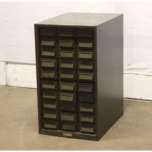 Worn green metal addressograph. 30 bin drawers with slots. Made by AM International.