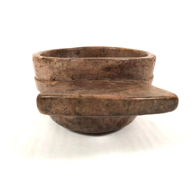 A sculptural and functional early primitive carved bowl, or trencher, with wonderful patina, of circular form with a...