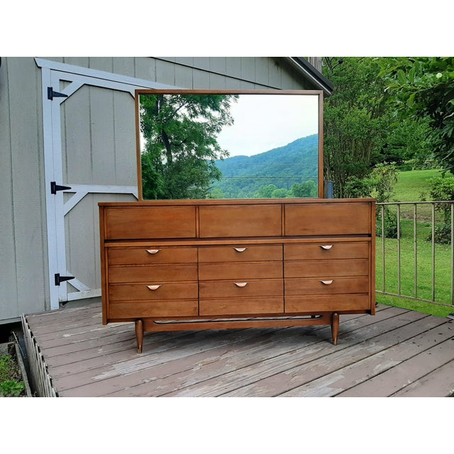 Item offered is a Mid Century Modern Hooker Furniture Co. Mainline 9 drawer Walnut dresser with mirror. The case sets on a...
