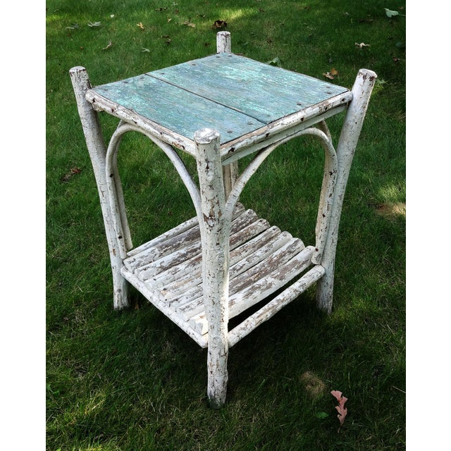 Sweet, small rustic Adirondack accent table with decorative bent wood on sides. The aged white and green paint just adds...