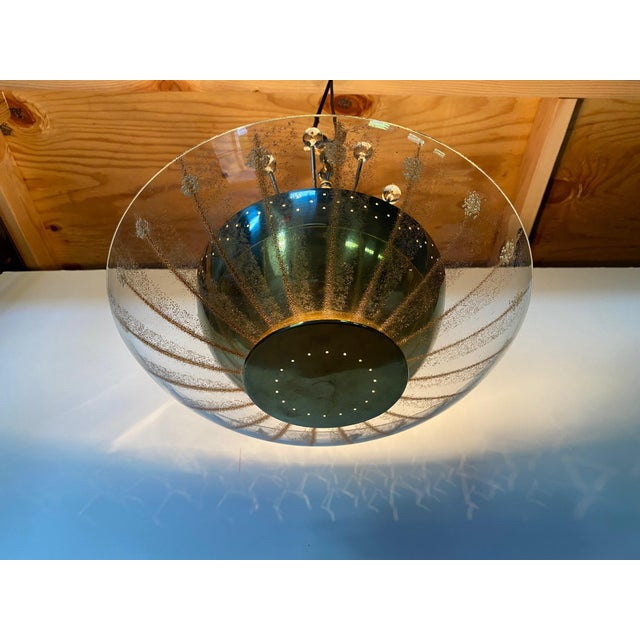 A fabulously designed take on a Mid-Century Modern Sputnik chandelier having pierced brass bowl and enameled glass shade...