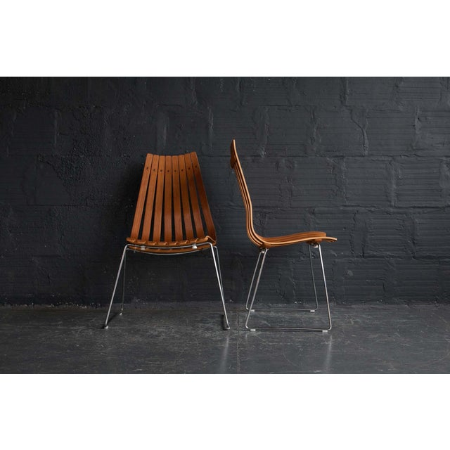 """A pair of Scandia chairs by Hans Brattrud that are made out of wood. Dimensions: 19"""" W 