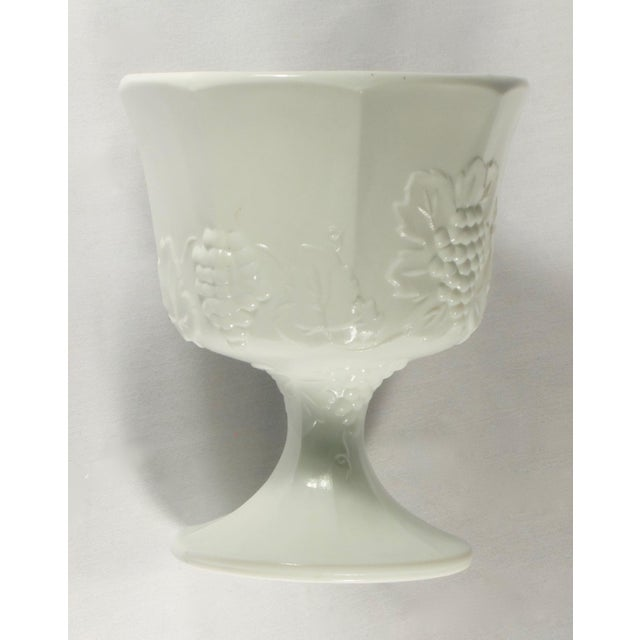 Vintage pedestal milk glass urn/ planter detailed with a raised grapevine motif. Base measures 4 inches in diameter.
