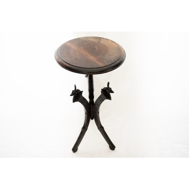An Eastlake style wooden plant stand featuring three carved deer heads. General wear and scratches throughout. Would...